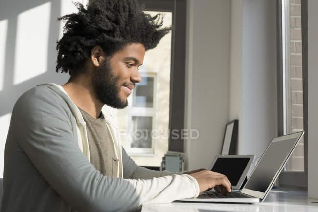 Homem usando laptop e tablet — Fotografia de Stock