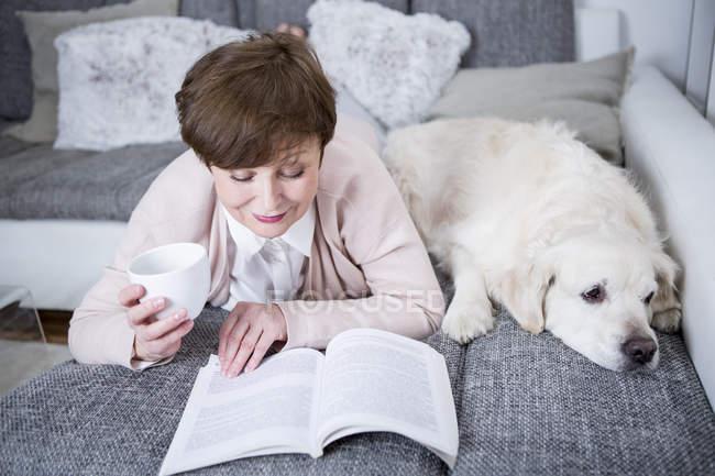 Mulher sênior, deitado no sofá com o cachorro — Fotografia de Stock