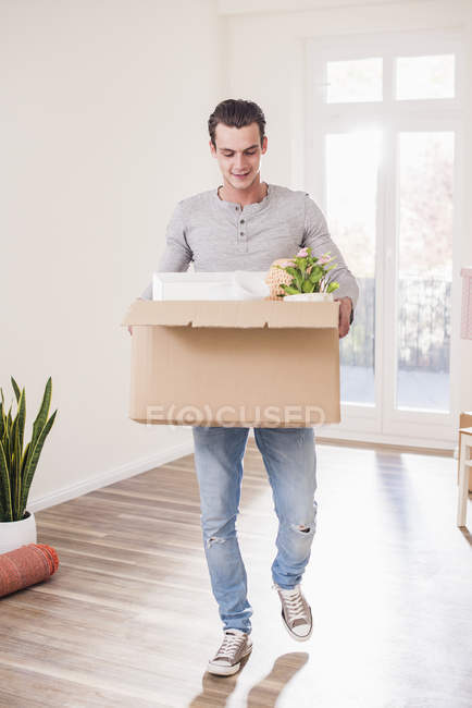 Young man carrying cardboard box in new home — Stock Photo
