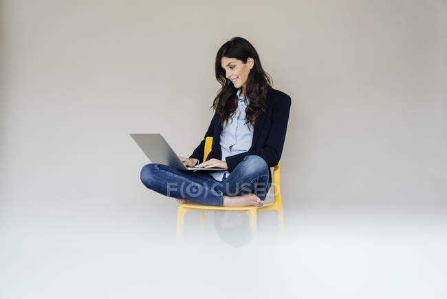Businesswoman sitting on chair and using laptop — Stock Photo