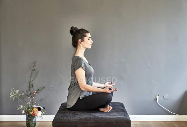 Женщина сидит в гостиной и занимается йогой — стоковое фото