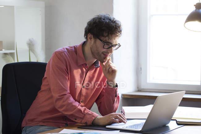 Man in glasses using laptop — Stock Photo
