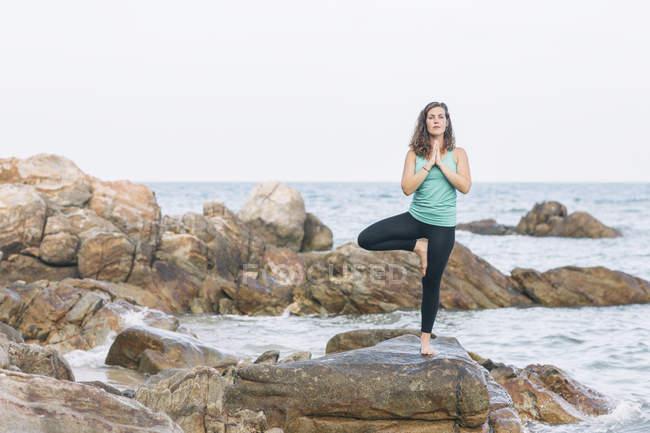 Woman practicing yoga on rock — Stock Photo
