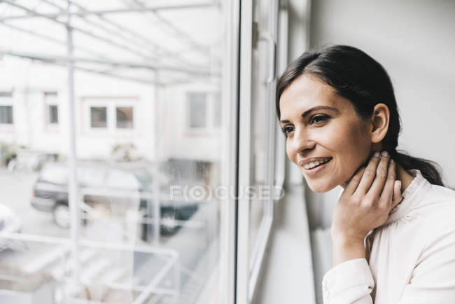 Woman looking out of window — Stock Photo
