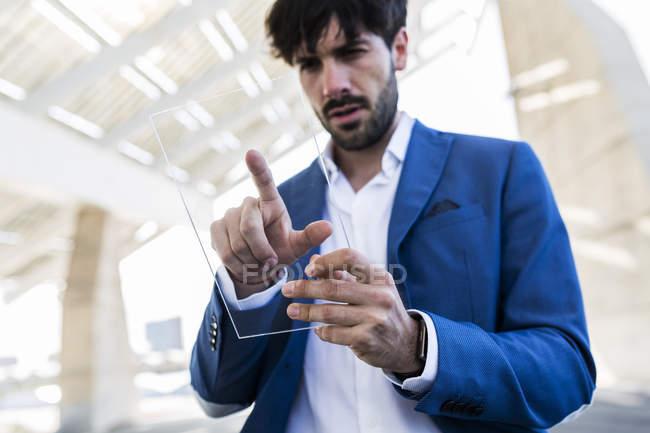 Businessman using futuristic portable device — Stock Photo