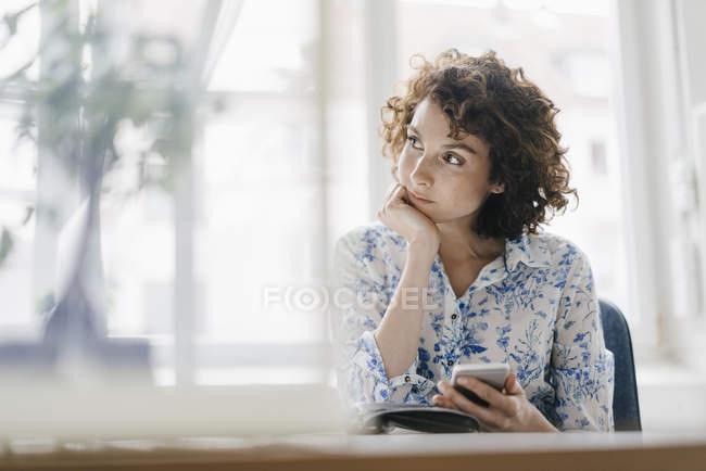 Geschäftsfrau sitzt mit Smartphone und Tagebuch — Stockfoto