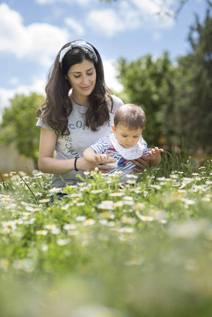 Mère et bébé fils sur le champ fleuri — Photo de stock