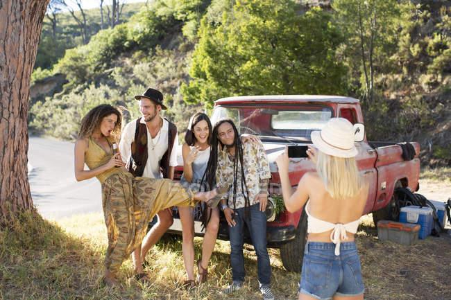 Счастливые молодые люди фотографируются возле фургона — стоковое фото