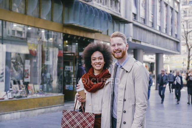 Счастливая пара, стоящая с сумкой — стоковое фото