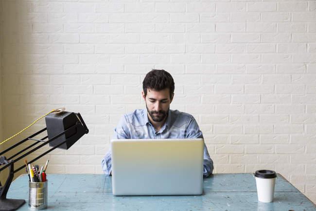 Homme sérieux travaillant avec son ordinateur portable — Photo de stock