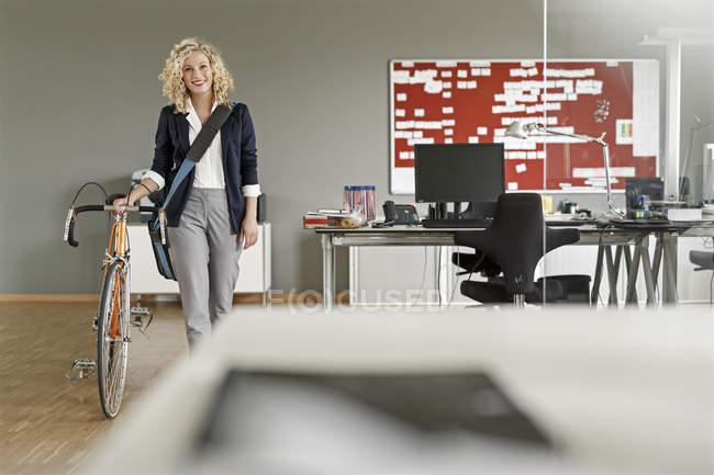Женщина с велосипедом в офисе — стоковое фото