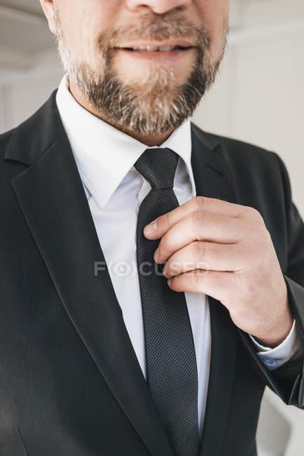 Businessman fastening tie — Stock Photo
