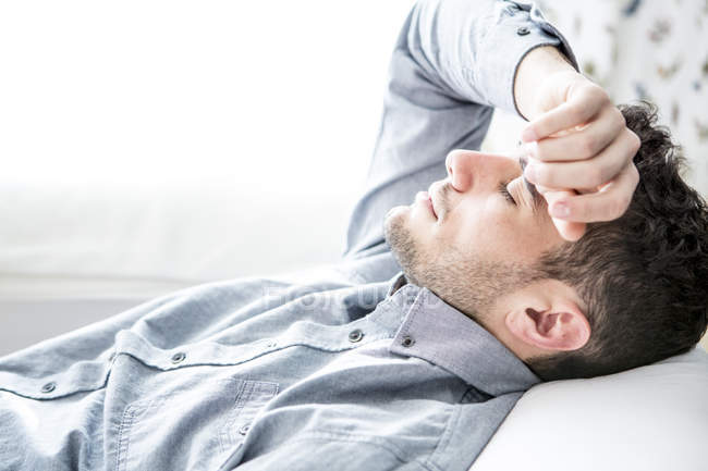 Man lying on couch with closed eyes — Stock Photo