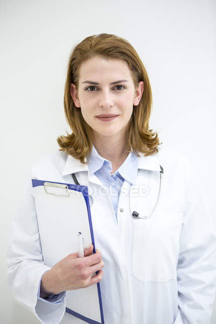 Female doctor holding clipboard — Stock Photo