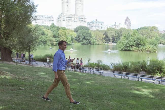 Uomo che cammina con smartphone e auricolari — Foto stock