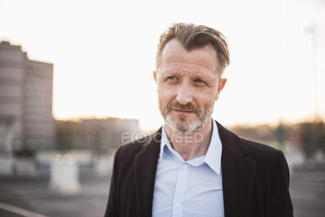 Businessman standing at sunset — Stock Photo