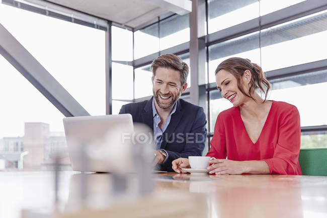 Colleagues sharing laptop in office — Stock Photo