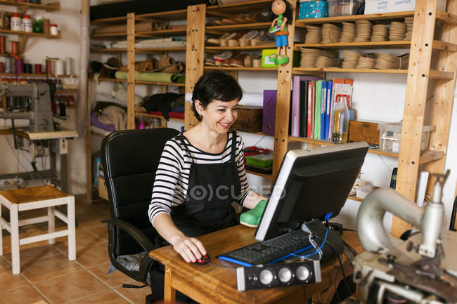 Smiling shoemaker using computer — Stock Photo