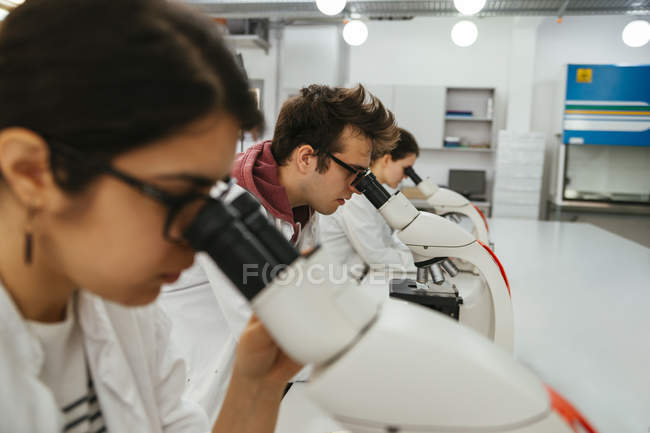 Technicians using microscopes in lab — Stock Photo