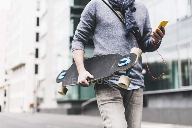 Businessman carrying skateboard — Stock Photo