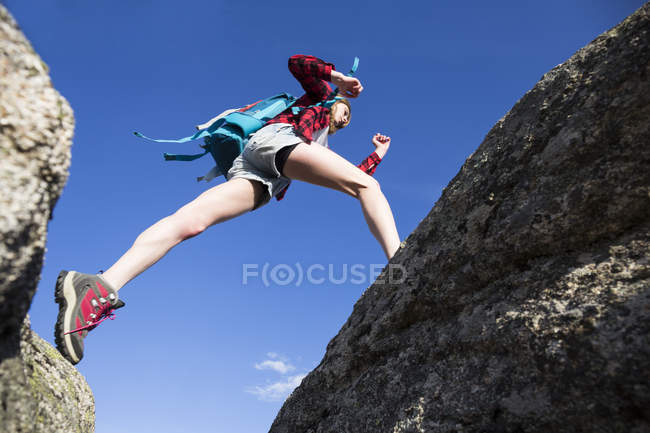 Woman with backpack jumping between rocks — Stock Photo