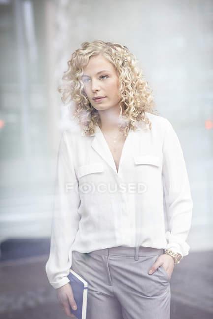Ritratto di attraente donna d'affari bionda dietro il vetro della finestra — Foto stock