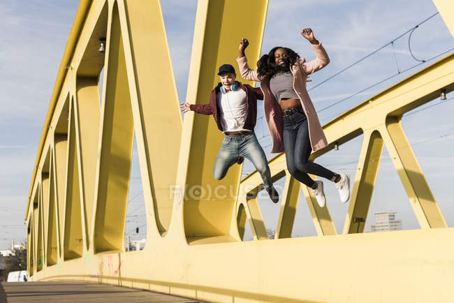 Couple jumping on bridge — Stock Photo