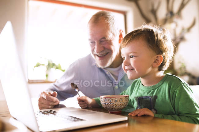 Grandfather and grandson using laptop — Stock Photo