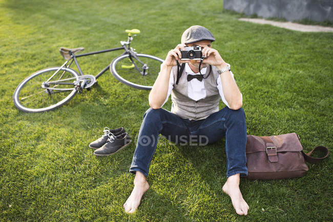 Businessman taking picture with retro camera — Stock Photo