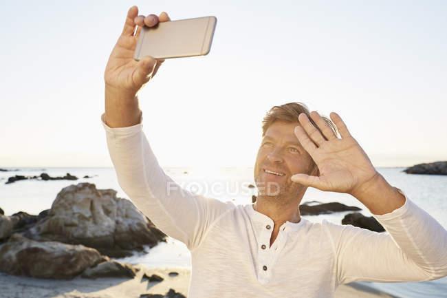 Lächelnder Mann nehmen Selfie am Strand — Stockfoto