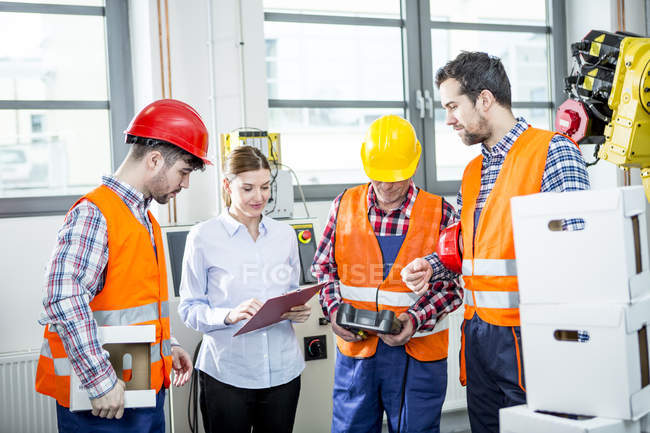 Staff discussing in factory with industrial robot in background — Stock Photo