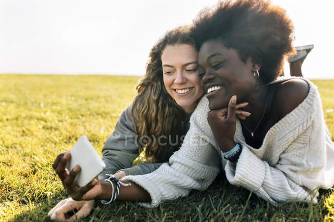 Beste Freunde liegen und nehmen selfie — Stockfoto