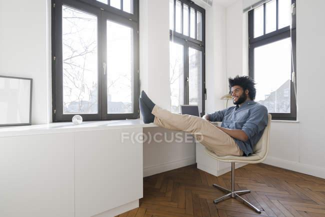 Homem sentado no quarto vazio minimalista — Fotografia de Stock