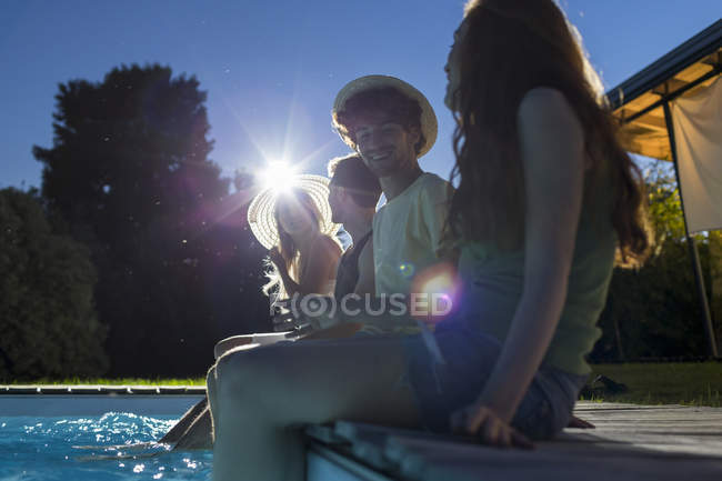 Друзі, сидячи біля басейну — стокове фото