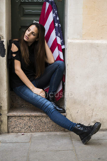 Woman sitting at entrance with American flag — Stock Photo