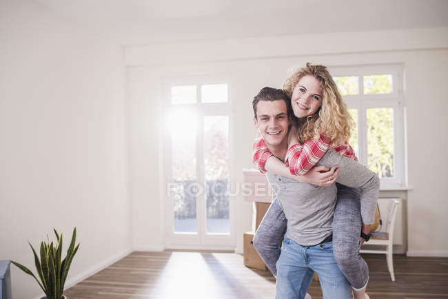 Portrait of happy young couple piggybacking at home — Stock Photo