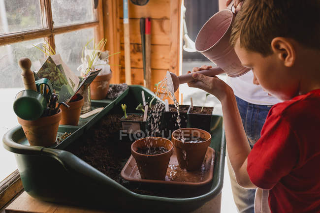 Father and son watering seeds — Stock Photo