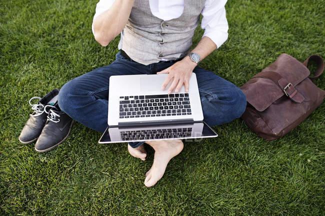 Geschäftsmann sitzt mit Laptop im Gras — Stockfoto