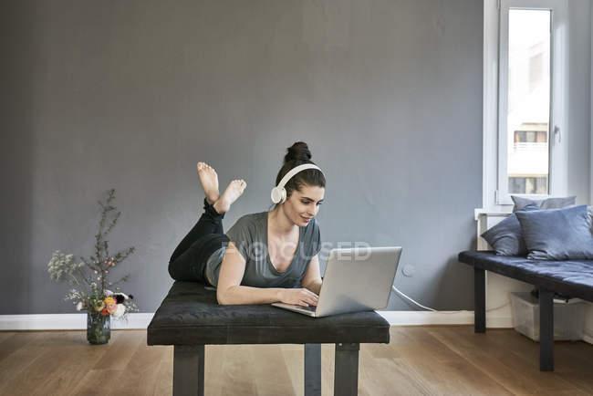 Frau mit Kopfhörer benutzt Laptop — Stockfoto