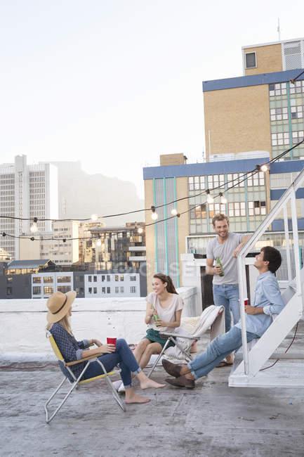 Freunde auf der Dachterrasse sitzen und trinken Getränke — Stockfoto