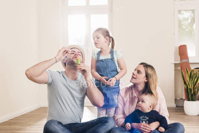 Young family blowing soap bubbles in new home — Stock Photo