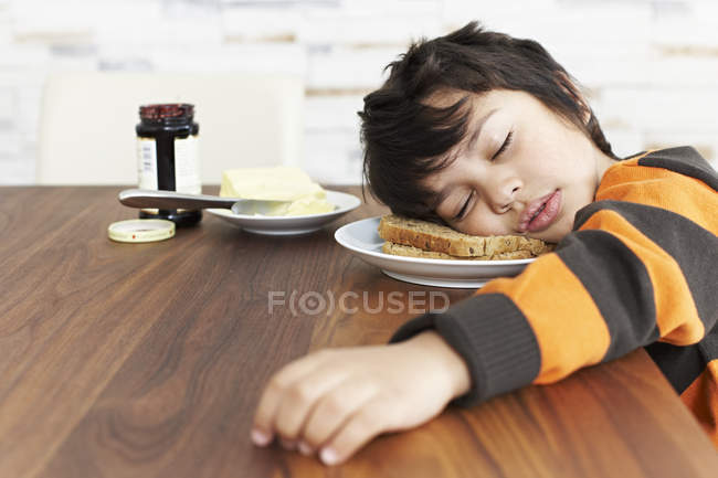 Garçon dormir à la table du petit déjeuner — Photo de stock