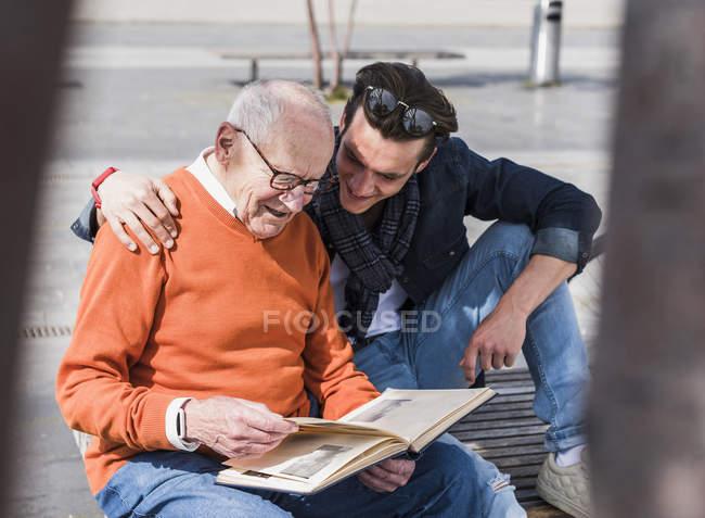 Senior man and grandson looking at photo album — Stock Photo