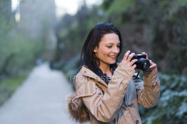 Young woman taking photos outdoors — Stock Photo