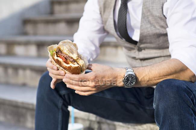 Бизнесмен ест гамбургер — стоковое фото