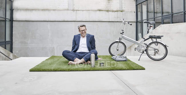 Businessman sitting with folding bicycle — Stock Photo