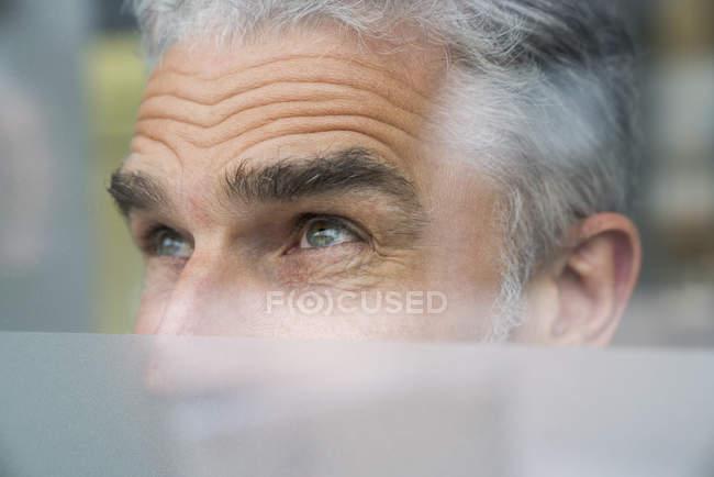 Businessman looking through glass pane — Stock Photo