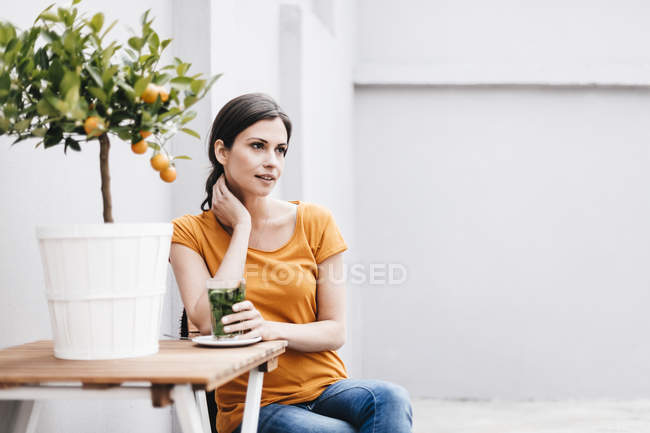 Woman relaxing at wooden table — Stock Photo