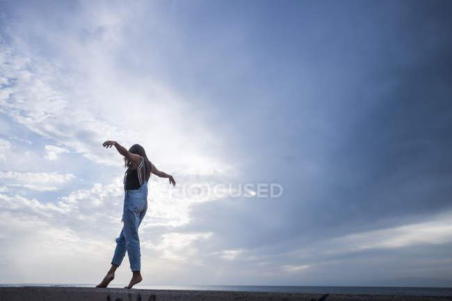 Woman with arms outstretched balancing on wall — Stock Photo