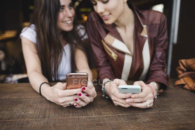 Duas mulheres jovens usando telefones celulares em um bar — Fotografia de Stock